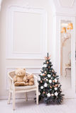 Small Christmas tree near chair with teddy bear Stock Photo