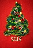 A small Christmas tree of tinsel, nuts, ribbons and ornaments. Gift for a Christmas tree, a vintage watch. 2018, Stock Photo