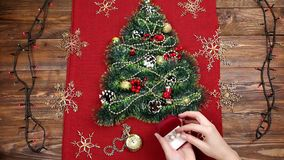 A small Christmas tree of tinsel, nuts, ribbons and ornaments. Gift for a Christmas tree, a vintage watch. 2018,. A small Christmas tree of tinsel, nuts, ribbons stock footage