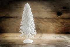 Small christmas tree from white flocked wire against a rustic wo. Oden background with large copy space, selected focus Royalty Free Stock Photo