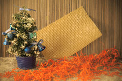 A small Christmas tree on a wooden background for postcards and Royalty Free Stock Photo