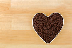 Small chunks of sweetened chocolate chips in heart shaped tin bo. Wl on wooden background with copyspace Royalty Free Stock Photo