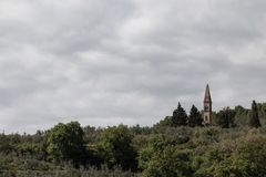 A small church bell tower emerging from a green forest, beneath Royalty Free Stock Image