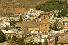 Small church surrounded by white houses in Albayzin neighborhood, Granada. Small church with bell tower surrounded by white traditional houses in Albayzin Royalty Free Stock Photos