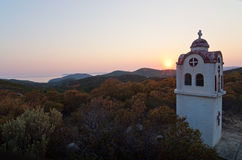 Small church or chapel with typical Greek landscape at sunset Stock Photos