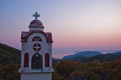 Small church or chapel with typical Greek landscape at sunset Royalty Free Stock Photos