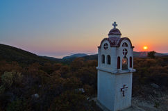 Small church or chapel with typical Greek landscape at sunset Stock Photo