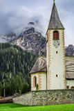 Small church in cloudy mountain Dolomites, Italy Stock Image