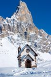 Small church in front of peak in Passo Rolle Stock Photo