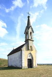 Small church on hill. Small church on top of a hill, with blue sky clouds in background Royalty Free Stock Image