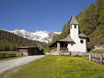Small church and log cabins in the austrian alps Royalty Free Stock Images