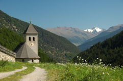 Small church in the mountains. A small church in the mountains on a sunny day. Forested mountainsides and a snow-covered peak in the background Stock Photo