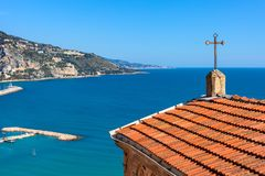 Small church overlooking Mediterranean sea and shoreline of Ment. Church roof with cross overlooking Mediterranean sea and shoreline of Menton - small town on Royalty Free Stock Photo