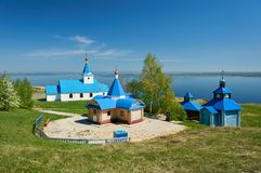 A small church painted with blue paint against the background of the sea and the blue sky on a sunny day. Royalty Free Stock Photos
