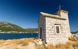 Small church on the rock, sea in the background Royalty Free Stock Image