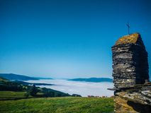 Small church of rocks and stones with a cross at the top, in fro. Nt of a green grass ranch over the clouds with cows pasturing and mountains at the background stock images