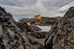 Small church of Santa Catalina on the coast of Mundaca village in Biscay during a cloudy day. Spain stock photos