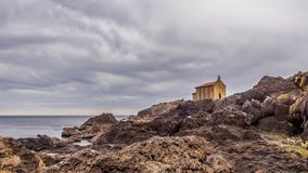 Small church of Santa Catalina on the coast of Mundaca village in Biscay during a cloudy day. Spain royalty free stock image