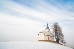 Small church on snowy hill. Slovenia. Skofja Loka area, St. Andrew Church Stock Photo