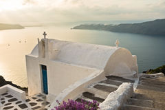 Small church at sunset with Oia village in background, Santorini island Stock Images