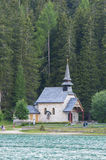 Small church in the woods on the lake shore, Dolomites, Italy Stock Photography