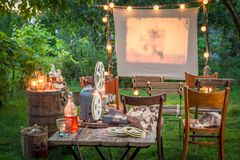 Small cinema with retro projector in the evening. In summer Stock Image