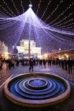 A small circular shaped fountain in Victory Square in Timis. A small circular shaped fountain under a decorating lighting tent and the Opera House in the Royalty Free Stock Image