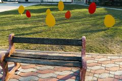 Small city bench standing on a pavement near a tree stock images