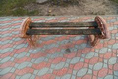 Small city bench standing on a pavement near a tree royalty free stock images