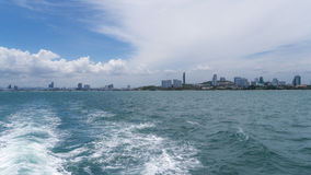 Small city view across rippling waves. Pataya Thailand pictures across a large body of water, rippling waves, and some clouds in depth Royalty Free Stock Photos