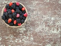 Small clay bowl of freshly assorted berries royalty free stock photo