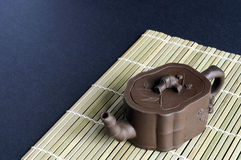 Small clay teapot on bamboo mat. A small clay teapot rests on a bamboo mat Stock Images