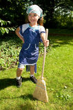 Small cleaning lady with broom in spring Royalty Free Stock Photo