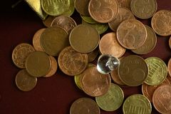 A small clear crystal gemstone on a heap of money gold coins. royalty free stock photography