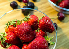 Small clear glass bowl of red organic strawberries standing on a chopping board Royalty Free Stock Photo