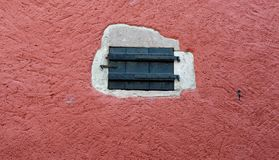Small closed door in red plaster wall. Texture of a small closed door in red plaster wall Royalty Free Stock Photo
