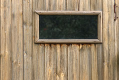 A small closed window in unpainted rustic wooden wall of a wooden house. Horizontal view Royalty Free Stock Photography