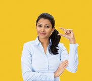 Small. Closeup portrait, beautiful young woman showing small amount gesture with hands,  yellow background. Human emotion facial expression feelings, body Stock Photo