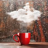 Small cloud raining into a cup.  royalty free stock image