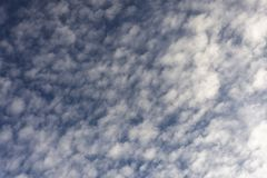 Blue sky. sunny day. clouds. Small clouds in a sunny day with a dark blue backgrouund stock photography