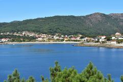 Small coastal village in a bay with beach, mountain and forest. Galicia, Spain, sunny day. La Coruna province, Galicia, Rias Altas, Spain. Bay with small stock photography