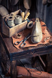 Small cobbler workplace with shoes, laces and tools Royalty Free Stock Photos