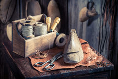 Small cobbler workplace with tools, leather and shoes Royalty Free Stock Photos