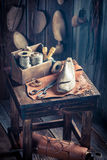 Small cobbler workshop with shoes, laces and tools Royalty Free Stock Images