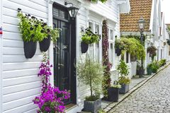 Traditional cobblestone street with wooden houses in the old town of Stavanger, Norway. Small cobblestone street with traditional white painted wooden houses on Stock Images