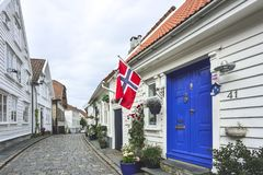 Traditional cobblestone street with wooden houses in the old town of Stavanger, Norway. Small cobblestone street with traditional white painted wooden houses on Stock Photography