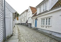 Traditional cobblestone street with wooden houses in the old town of Stavanger, Norway. Small cobblestone street with traditional white painted wooden houses on Royalty Free Stock Images