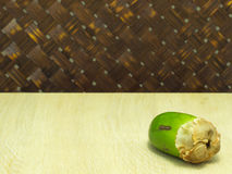 Small coconut isolated on table in weave background Stock Image