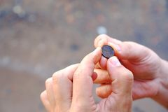 A small coin found in the sand on the shore of the water stock images