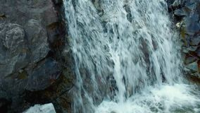 Small waterfall surrounded by trees in the mountains. Small cold waterfall surrounded by tress and grey rocks in the mountains stock footage